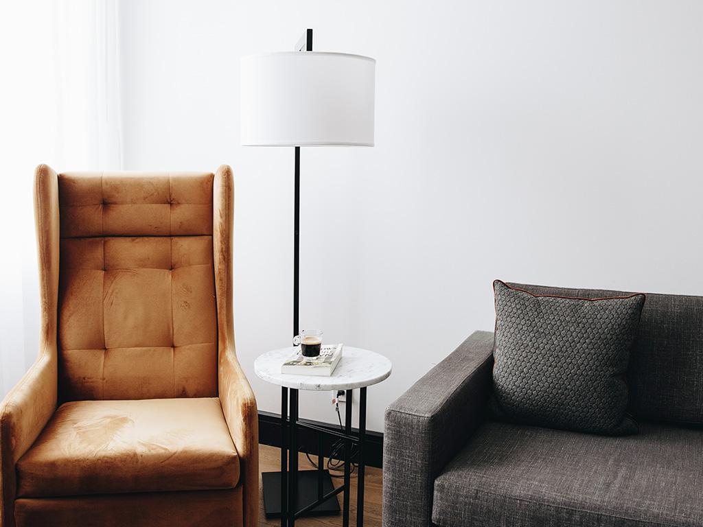 Deux chaises et une lampe dans l'une des chambres de l'Hôtel Place d'Armes.