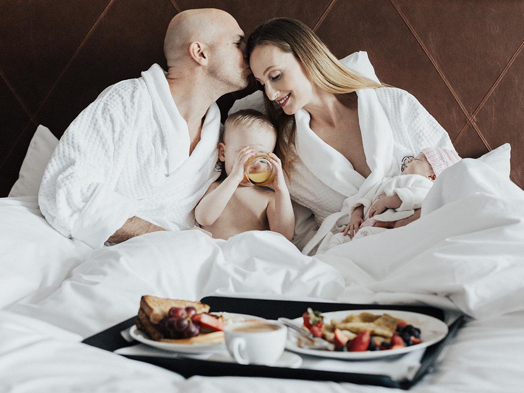 Deux parents et leurs enfants en train de prendre un petit-déjeuner au lit dans une chambre de l'Hôtel Place d'Armes