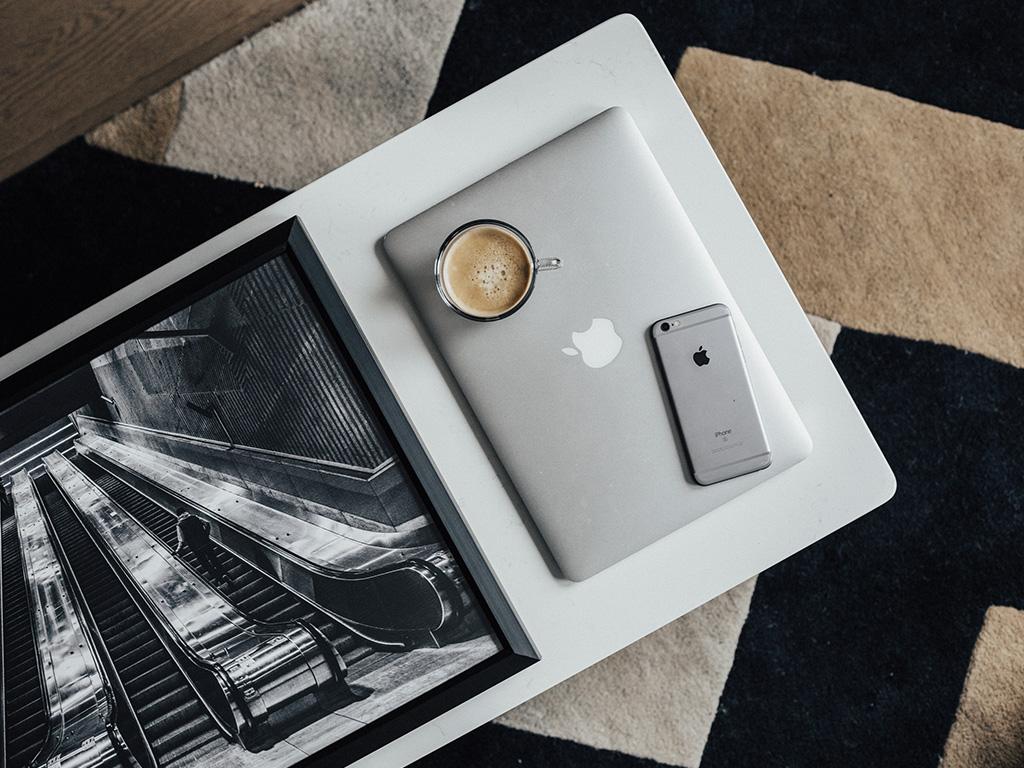 Un ordinateur portable, un téléphone portable et un café posés sur une table dans une chambre de l'Hôtel Place d'Armes