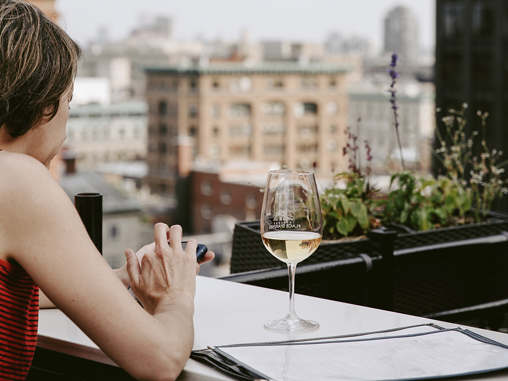 A girl having a glass of wine at Terrasse Place d'Armes with a view of Old Montreal